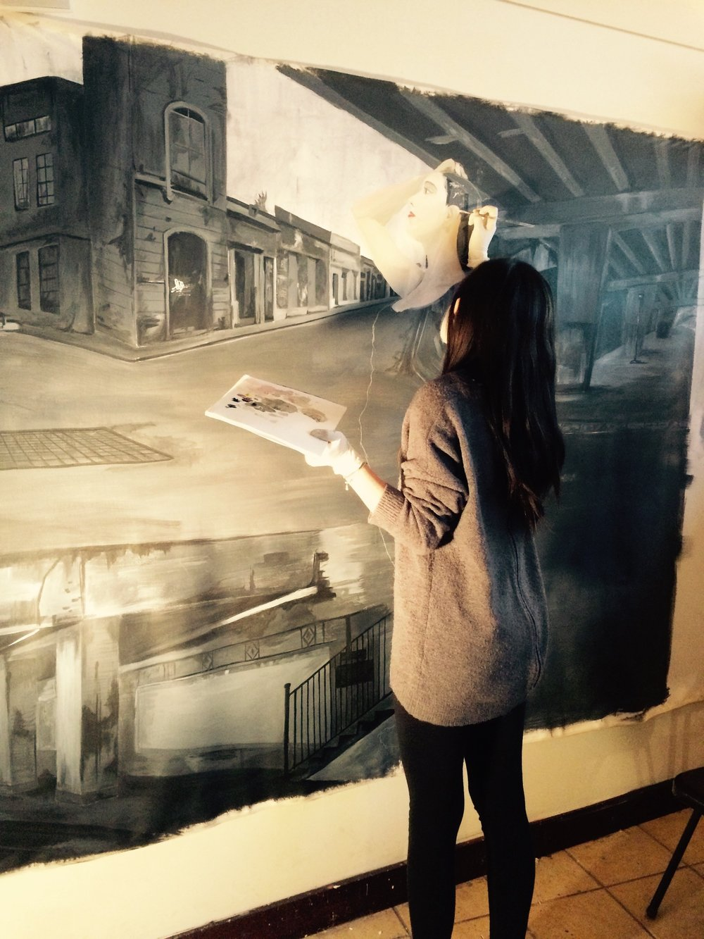 Student painting image of female over scene with buildings and overpass