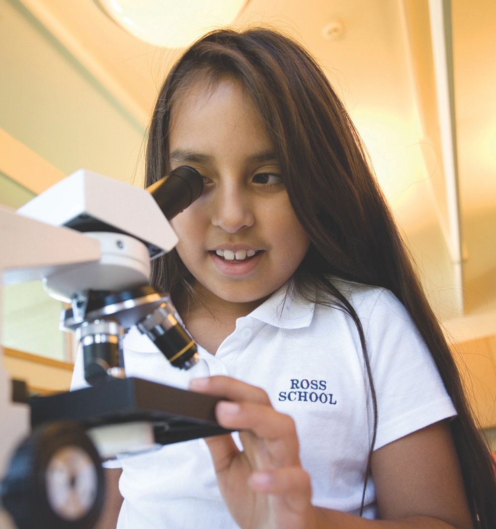 Elementary student looks through microscope eye piece during hands-on Science lesson.