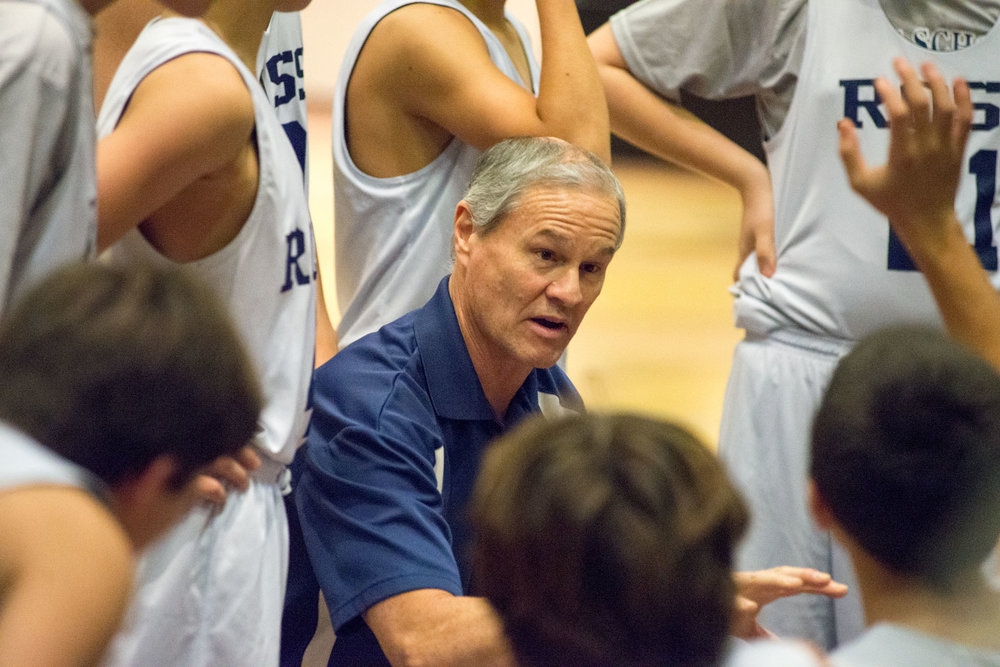 Ross High School Boys Basketball Coach Advising the Team During a Timeout Group Huddle.