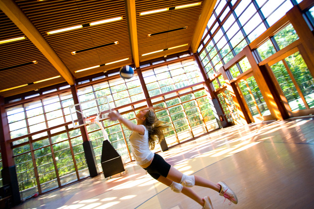 Ross High School volleyball player dives for volleyball in light-filled gym with floor to ceiling windows in background.