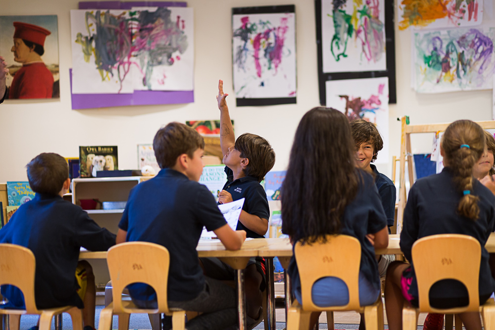 Ross Lower School students in Visual Arts class, surrounded by student artwork