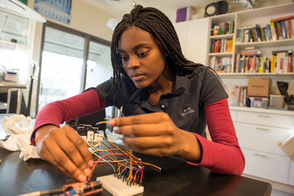 Female STEAM Innovation Lab student connecting a circuit board to a device with multiple wires.