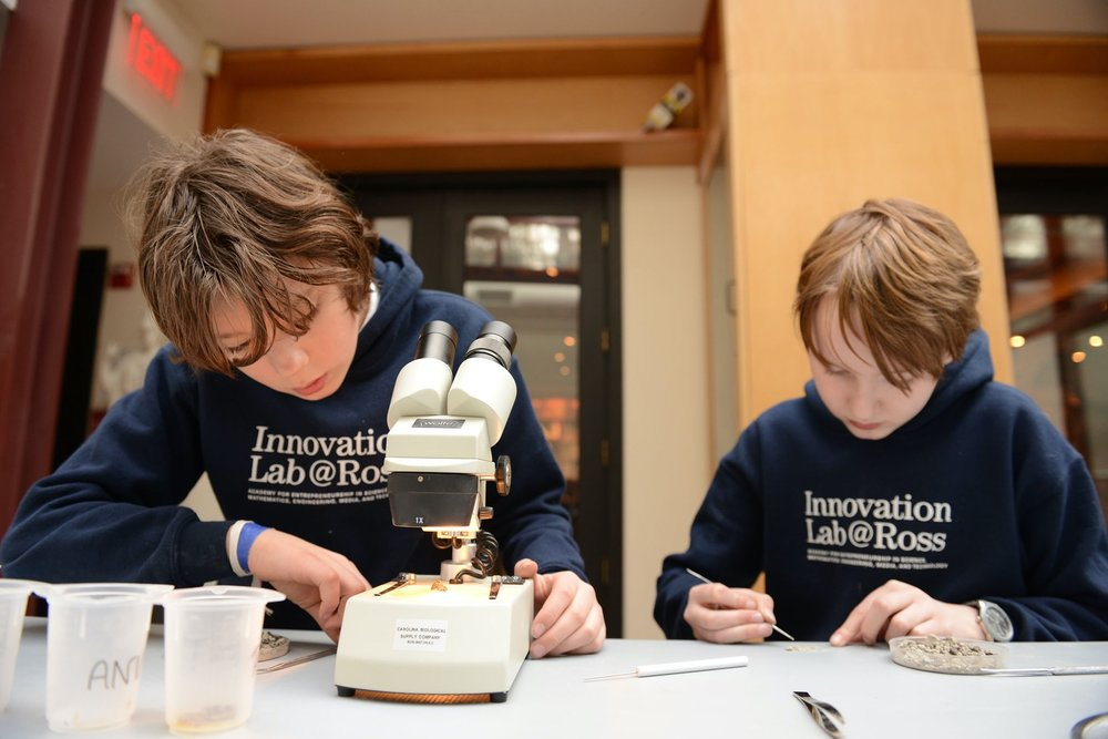 Two Ross STEAM Innovation Lab students seated at a table, one making adjustments to a microscope and the other preparing a specimen slide.