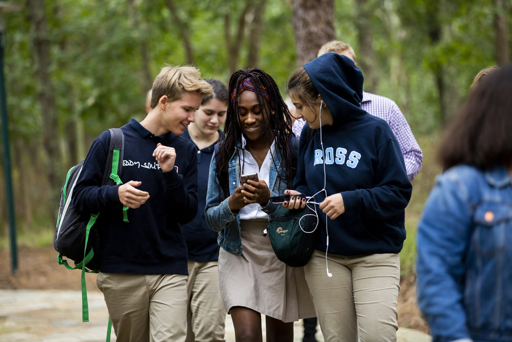 Ross Upper School students socialize between classes as they take the stone path that weaves through the beautiful woodland campus.