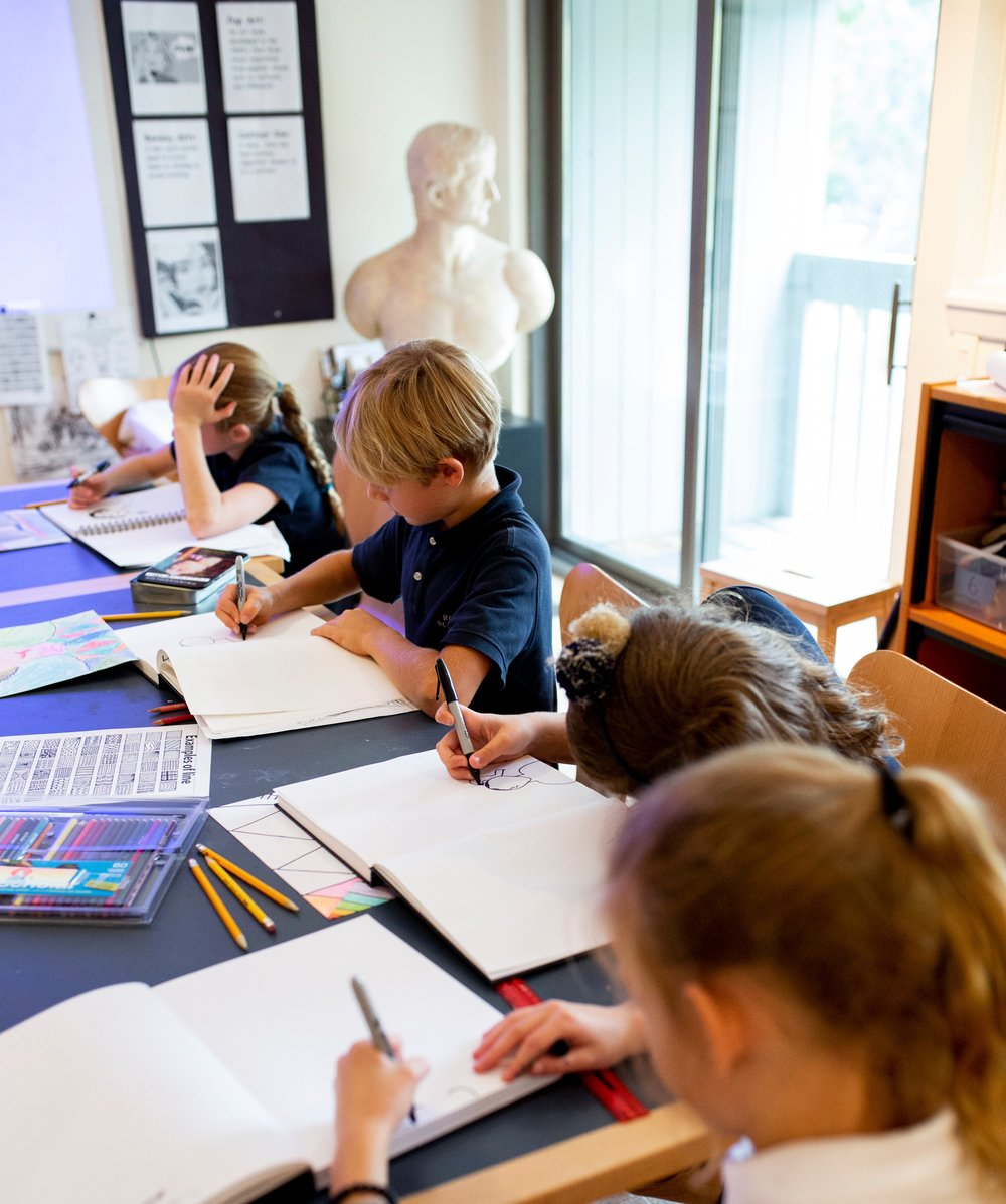 Ross elementary students work on sketches during Visual Arts class with classical bust in background.