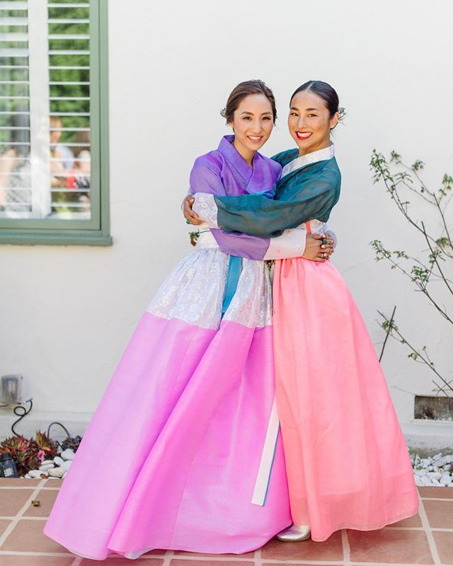 My sister @thegreta and I outside my house just before my Korean wedding ceremony in 2015 💕 So inspired by the vibrant hues of traditional Korean silk organza fabrics and embroidery. Wearing bespoke @meeheehanbok. ⠀⠀⠀⠀⠀⠀⠀⠀⠀ ⠀⠀⠀⠀⠀⠀⠀⠀⠀ ⠀⠀⠀⠀⠀⠀⠀⠀⠀ #sister #sisters #sistersister #sisters👭 #twopeasinapod #hugs #traditional #colorful #pinks #purple #dresses👗 #dresselegant #lowbun #flowerinhair #lipshade #sisterlylove #sisterlybonding #mylovelysister #traditionaldress #koreanstyle #koreanamerican #proudheritage #dowelookalike #loveyousomuch #popofcolor #whitebackground #proudsister #proudsis #wedding photo by @leilabrewster