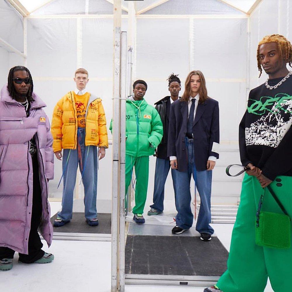 """Off-White - Virgil Abloh continue son ascension en conservant les codes qui ont fait sa réussite: silhouettes rétro-futuristes mixant les baggies taille-haute 90's, aux doudounes matelassées intégrales. Omniprésence des couleurs dans son oeuvre, et costumes aux épaules immenses en mode """"mafioso""""."""