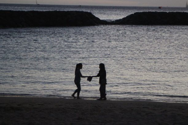 Two children at dusk on Ala Moana Beach
