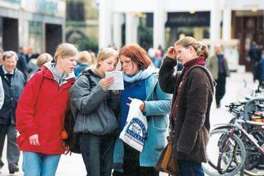 20_young_tourists_consult_paper.jpg
