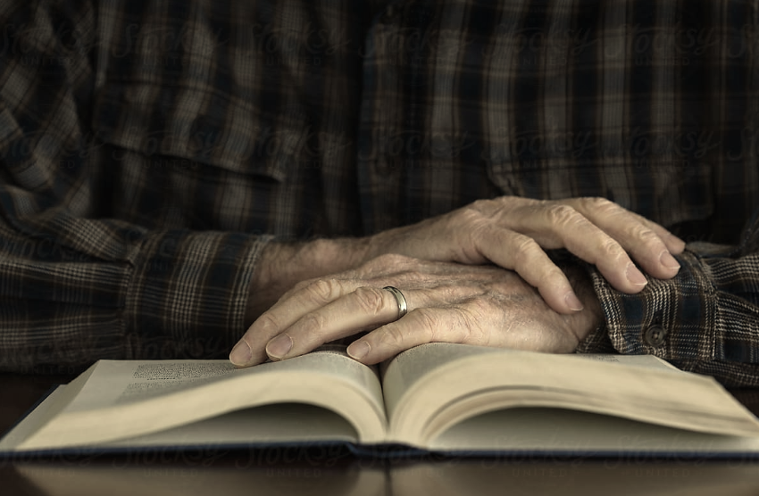 old man hands book.png