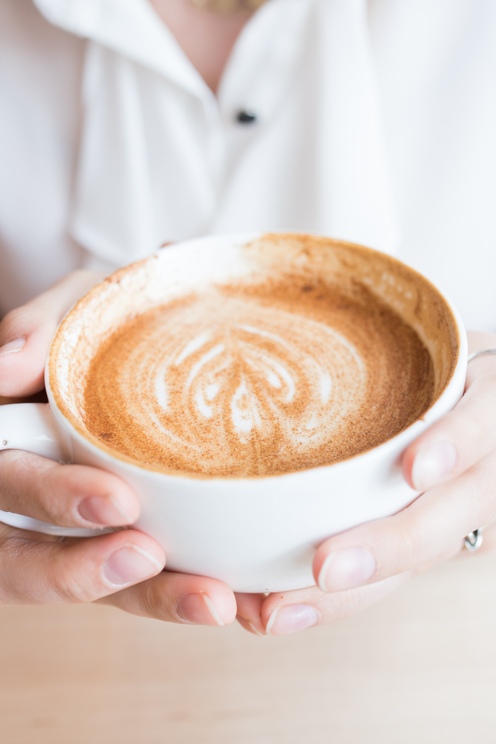 woman holding latte with milk art