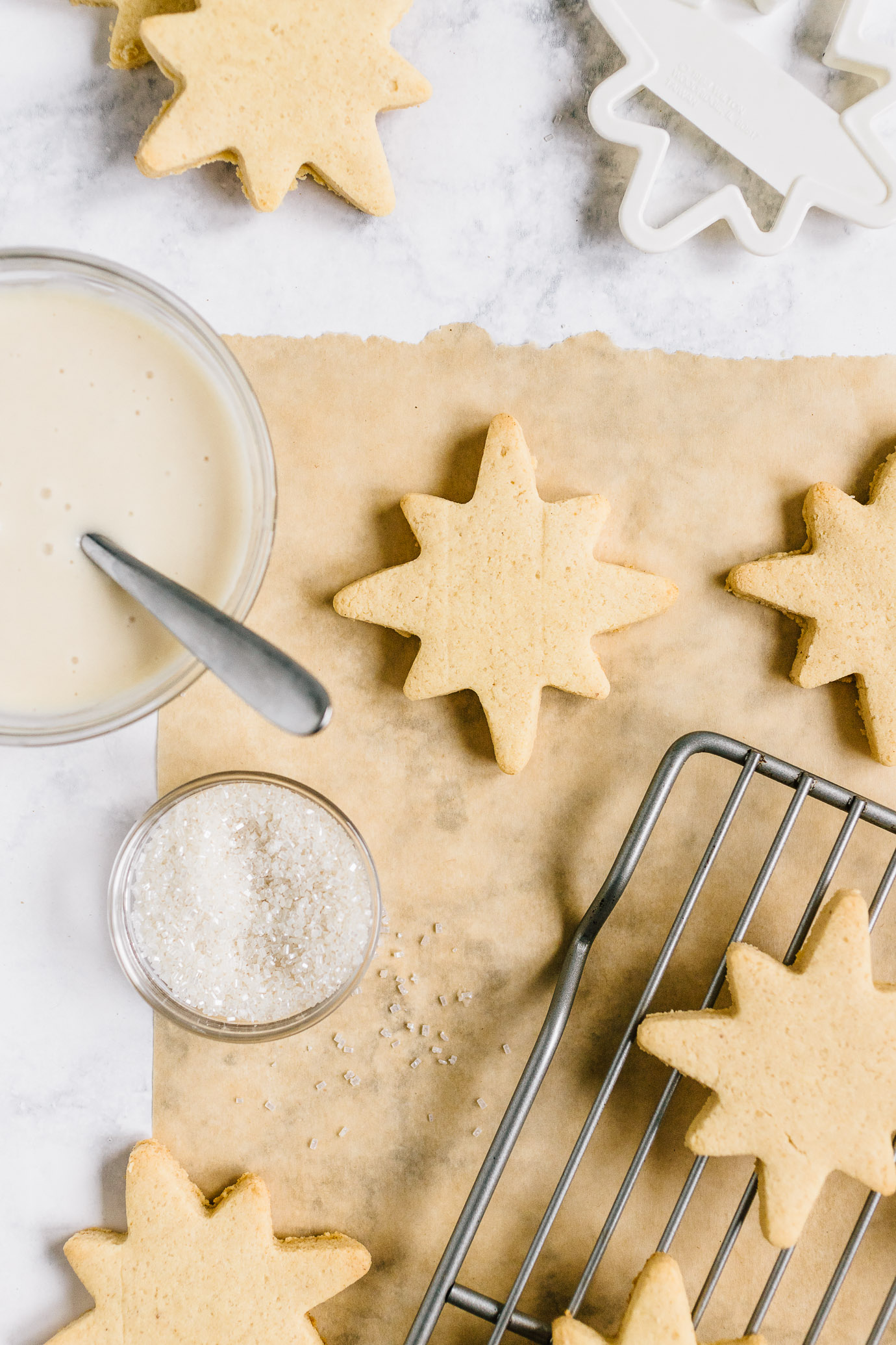 Almond Flour Sugar Cookies cut-outs on parchment paper with bowl of icing