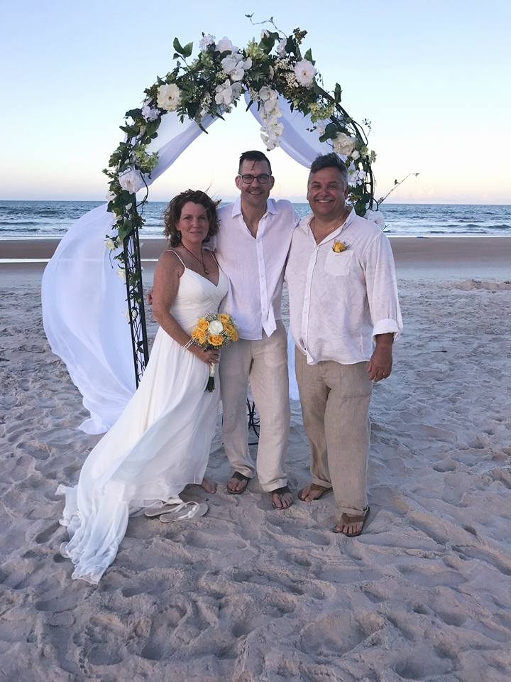 Newlywed couple smile with wedding officiant Sam in Ormond Beach, FL