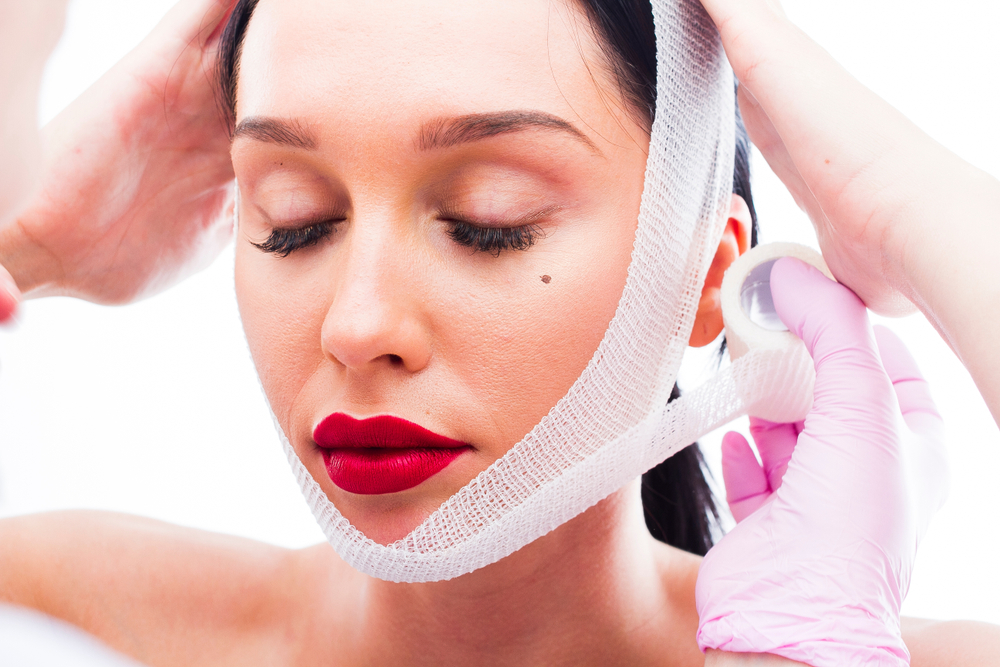 The doctor wraps the face of the patient with bandages after a facelift procedure.jpg