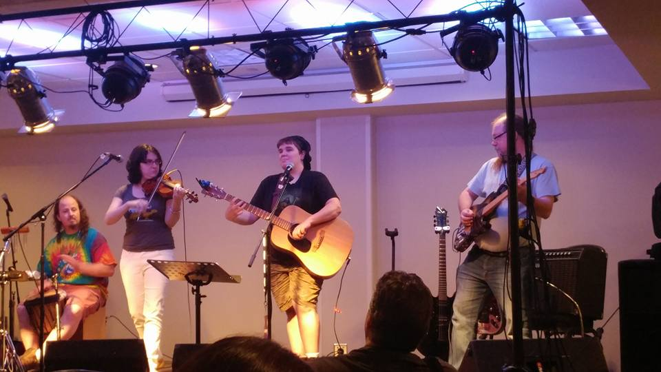 Beth performing with the Player Characters at CONvergence 2017. Left to right: Justin Hartley, Elizabeth Greenberg, Beth Kinderman, Dave Stagner.