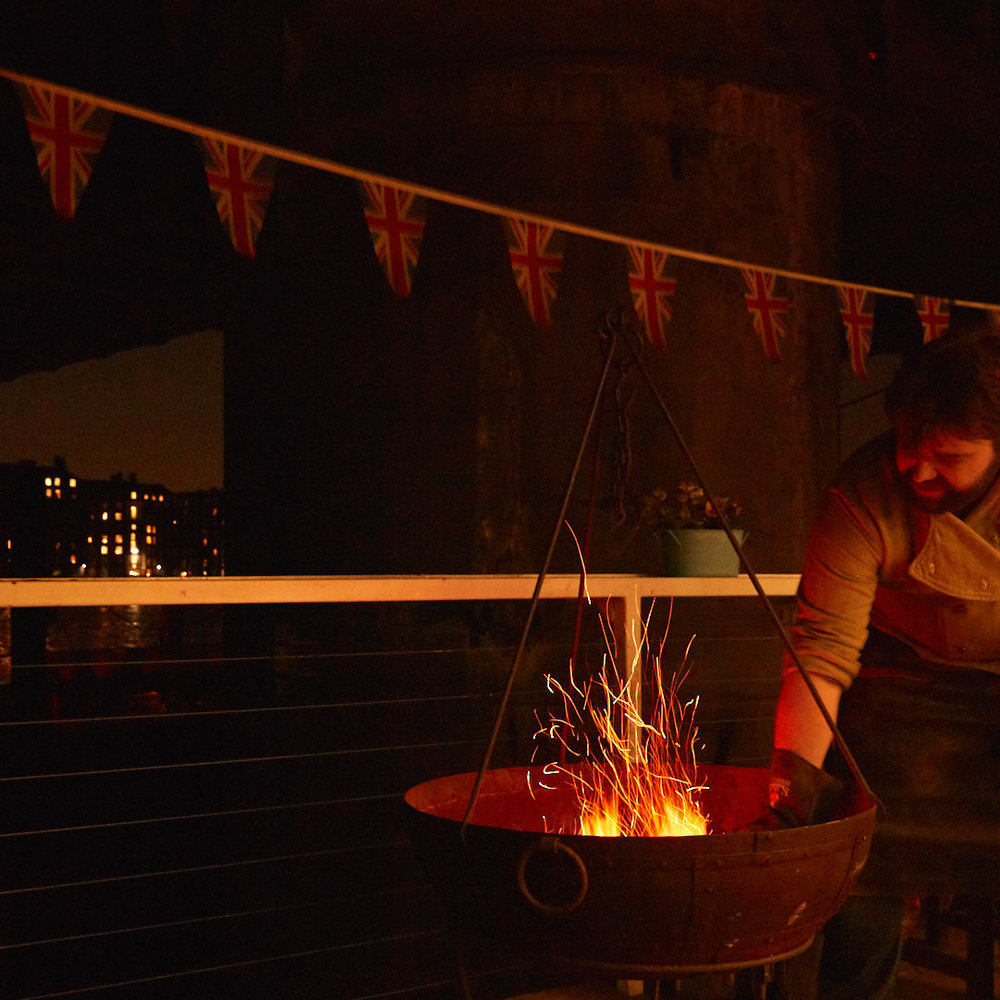 Dougy cooking on an open fire in London