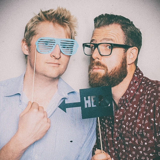 a blonde man and a brown haired man with a beard both with fun glasses Greg and Thom of The Snappening Podcast