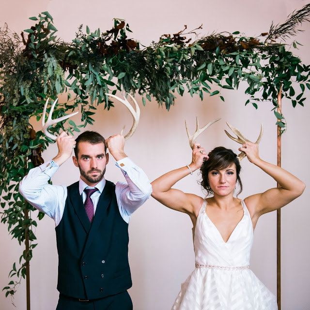 an angry bride and groom hold antlers up to their heads