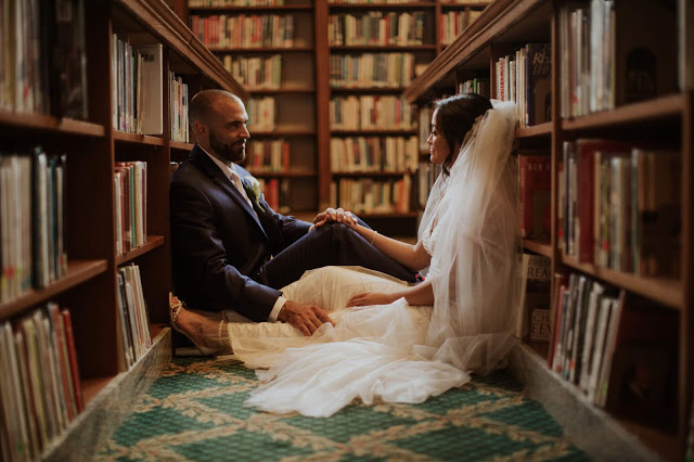 a bride and groom sit in the middle of a row of books in a library staring at each other