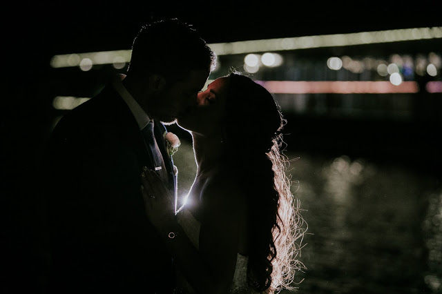 bride and groom kiss at night on waterfront while backlit by off camera flash and with tons of bokeh behind them broad ripple