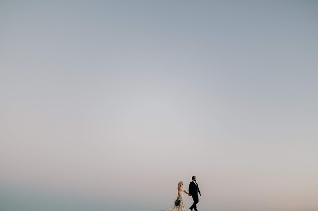 a minimalist photo of a bride and groom walking hand in hand with nothing but a big sky behind them