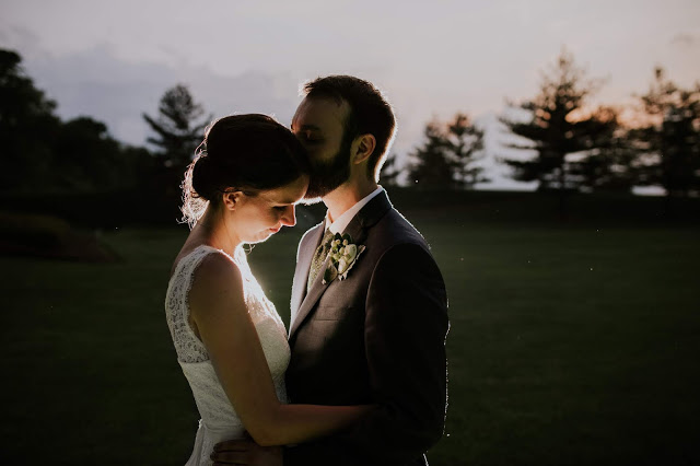 bride and groom kiss at dusk backlit by off camera flash with beautiful purple and orange hues in the sky above them