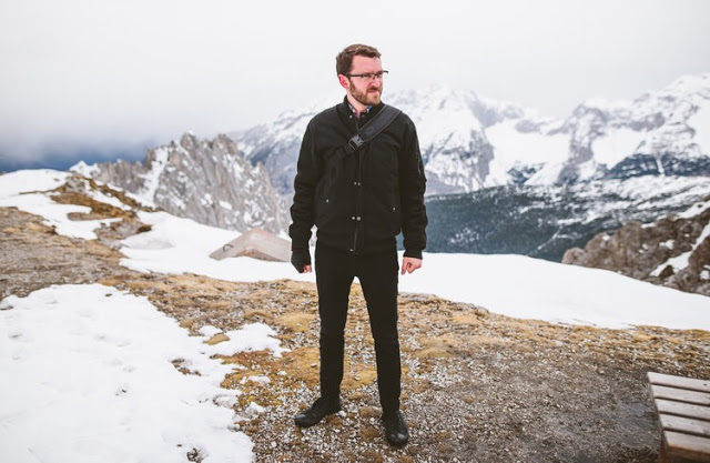 a man with glasses stands on top of a mountain with some snow while other taller mountains loom behind him