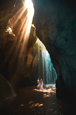 A couple walking through a gorge toward waterfalls in bali with cool and warm tones