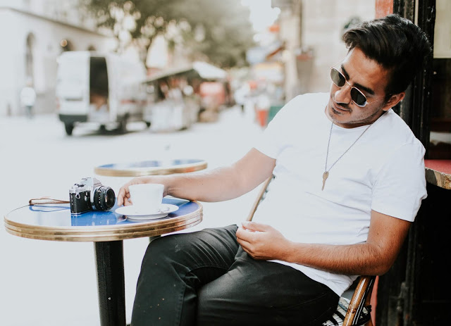 David Mendoza III or @heydoza sitting in a chair in paris wearing a white shirt and boots and sunglasses with a camera on the table in front of him