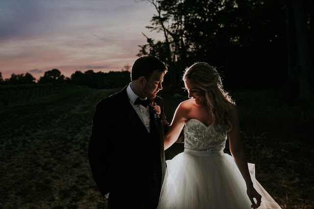 a man and a woman stand next to each other at sunset, they are back light by the light of the sun and by an off camera flash. there's tints of blue, purple, pink, red, and orange in the sky.