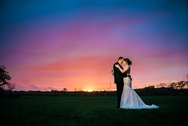 man in tux hugs woman in white dress in front of a gorgeous sunset in Indiana with some powerlines along the horizon, color transition from a warm yellow to a cold blue