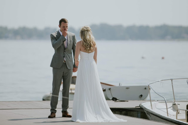 groom covers mouth in astonishment on dock on lake maxinkuckee in culver indiana