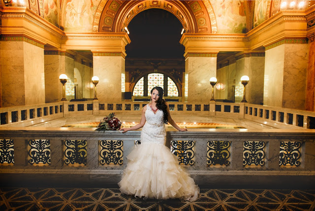a woman in a white wedding dress is framed by an arch in a magnificent building with warm tungsten tones