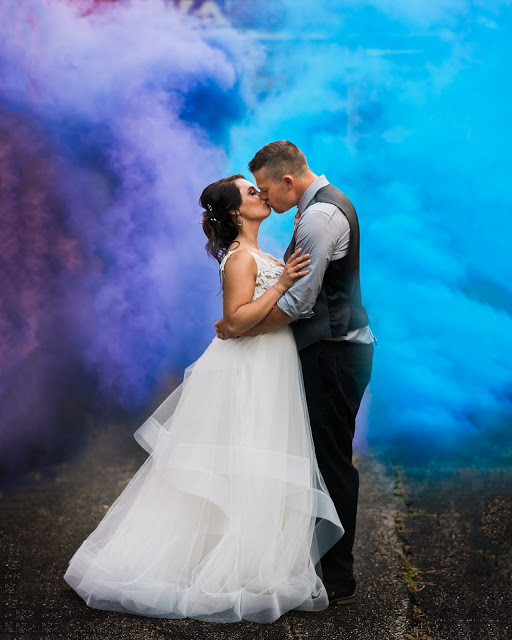 a young bride in white and a groom kiss in front of blue and purple smoke from smoke bombs