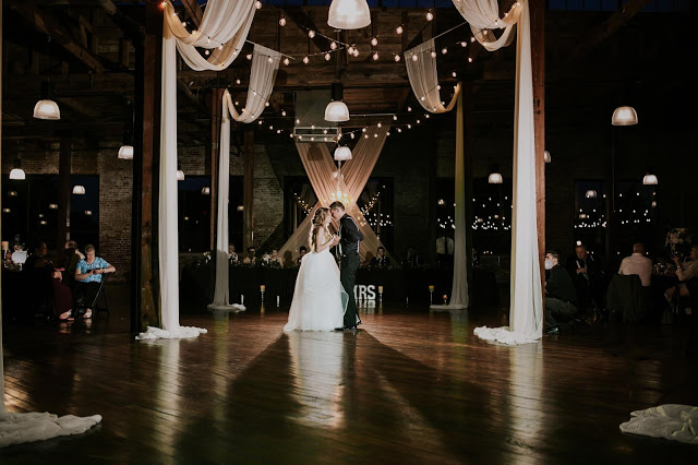 bride and groom dancing during first dance at biltwell event center with beautiful drapes