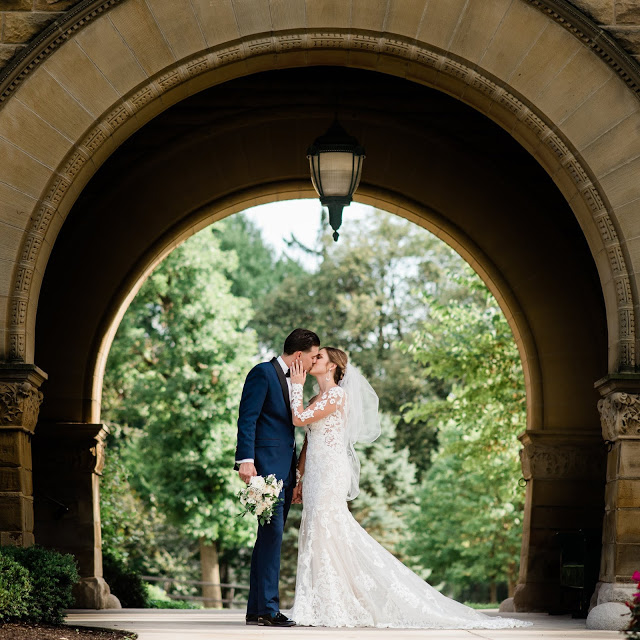 bride in white kisses groom in suit holding bouquet under a stone archway in a building