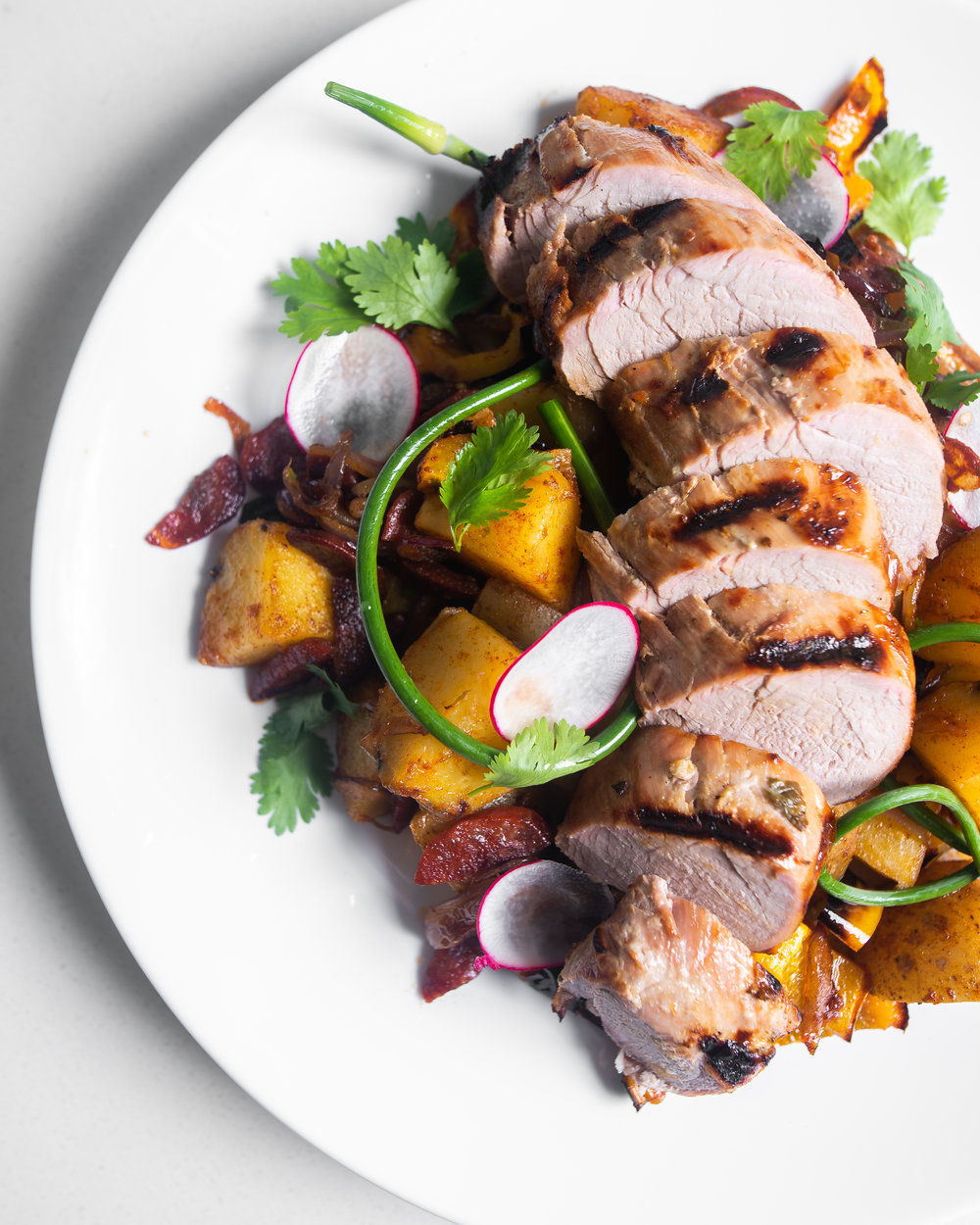 Grilled Pork Tenderloin on New Potato Hash with Chorizo, Radish and Garlic Scapes