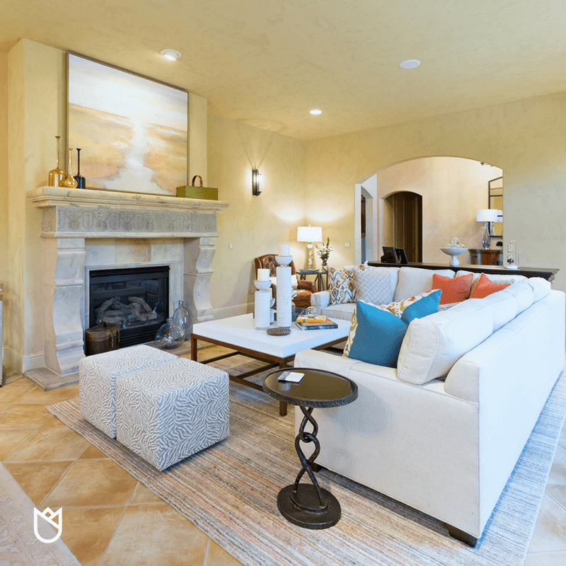 A white sectional atop a large wool rug anchors this room and give the off centered fireplace new meaning