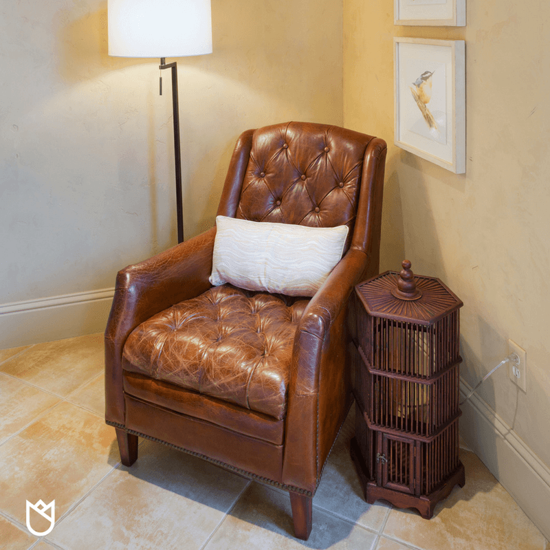 A lovely vintage leather chair is repurposed for a sweet little reading corner