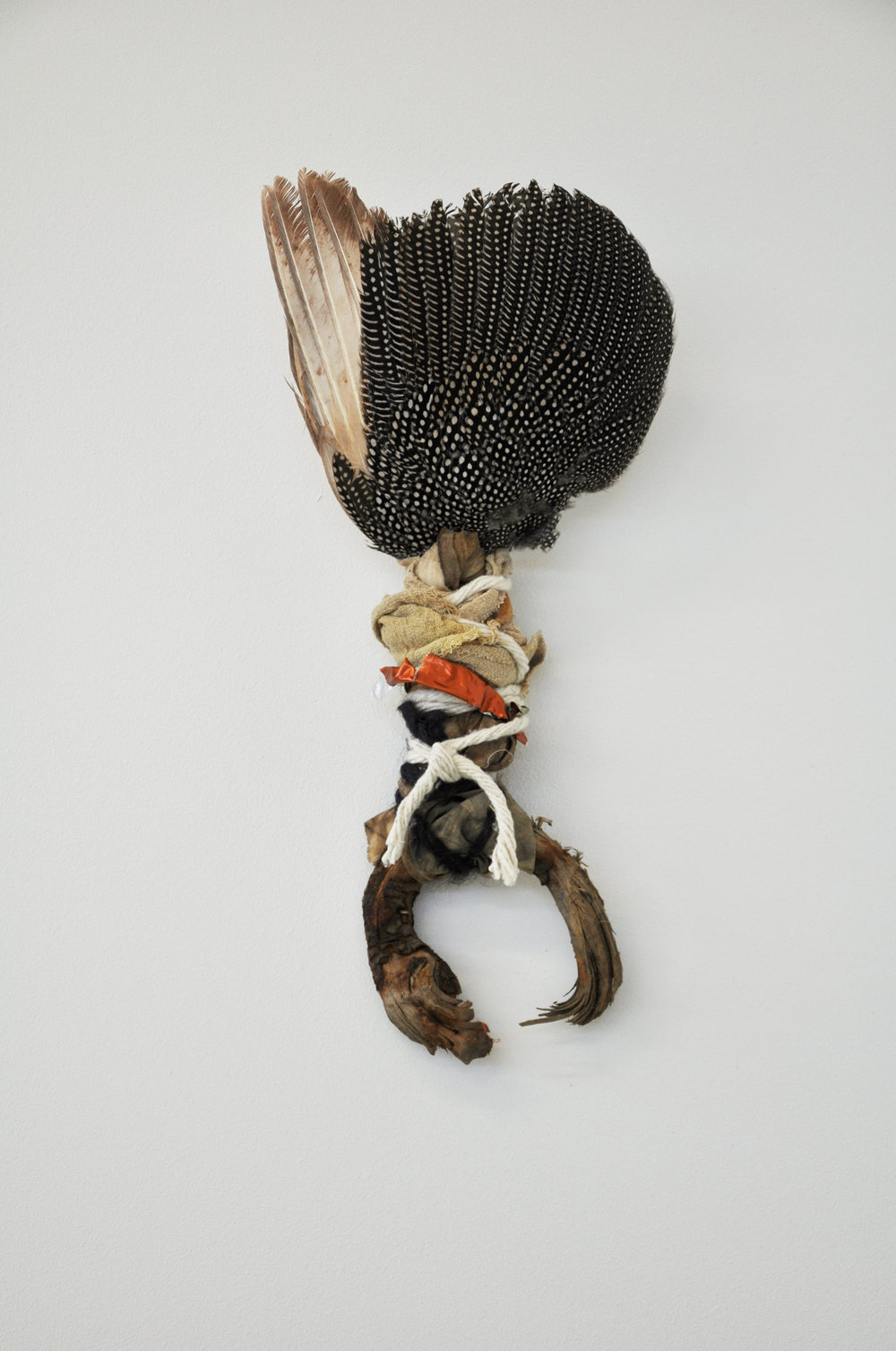 Praise Be,   2018  guinea fowl wing, wood, cloth, string, foil h55cm