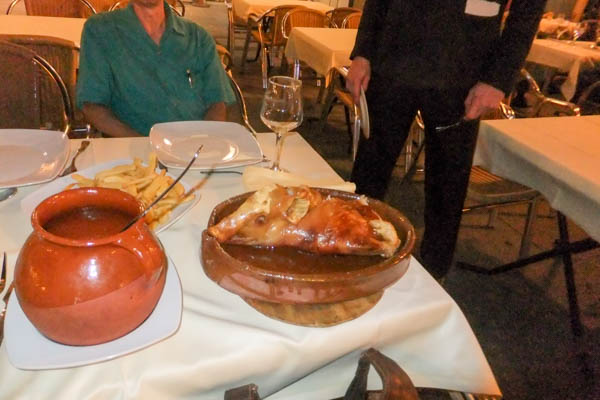 Having the specialty of Segovia, roast suckling pig. Note that the waiter is about to cut the pig with a dish.
