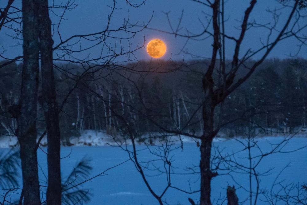 Full moon rising over snowy lake