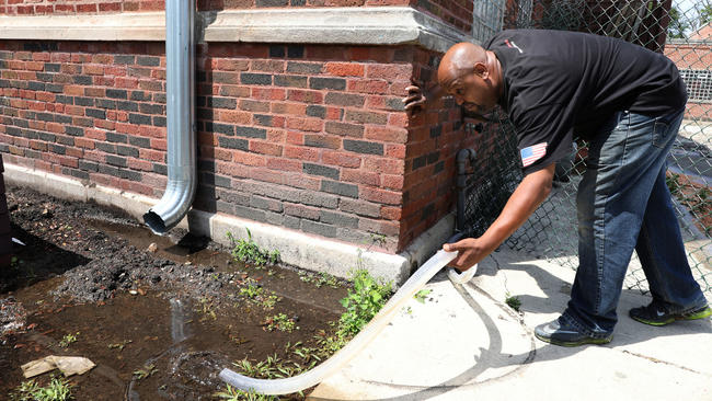 Steve Smiley, building and grounds supervisor for the Maywood Park District, said water pouring into a playground through a hose is being pumped from the basement of a nearby city-owned building.  Antonio Perez / Chicago Tribune