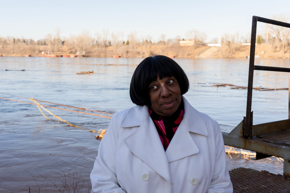Catherine Fleming sits near the Mississippi River for a portrait at the Upper Harbor Terminal site .  Photo by Iyana Esters | The Water Main
