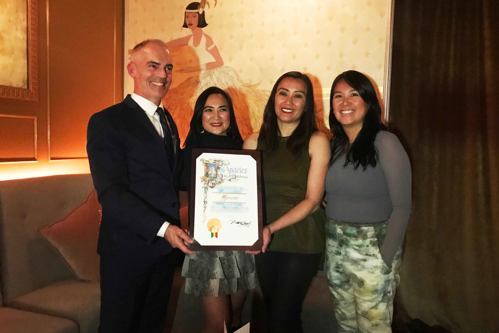 "Councilmember Mitch O'Farrell presents the City Certificate of Recognition to Genever owners Christine ""Tinette"" Sumiller, Patricia ""Tricia"" Perez, and Roselma Samala. Photo by Paola Mardo."