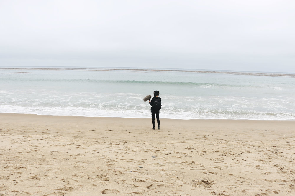 Host/producer Paola Mardo records sounds on a beach in Malibu, California. Photo by Patrick Epino.