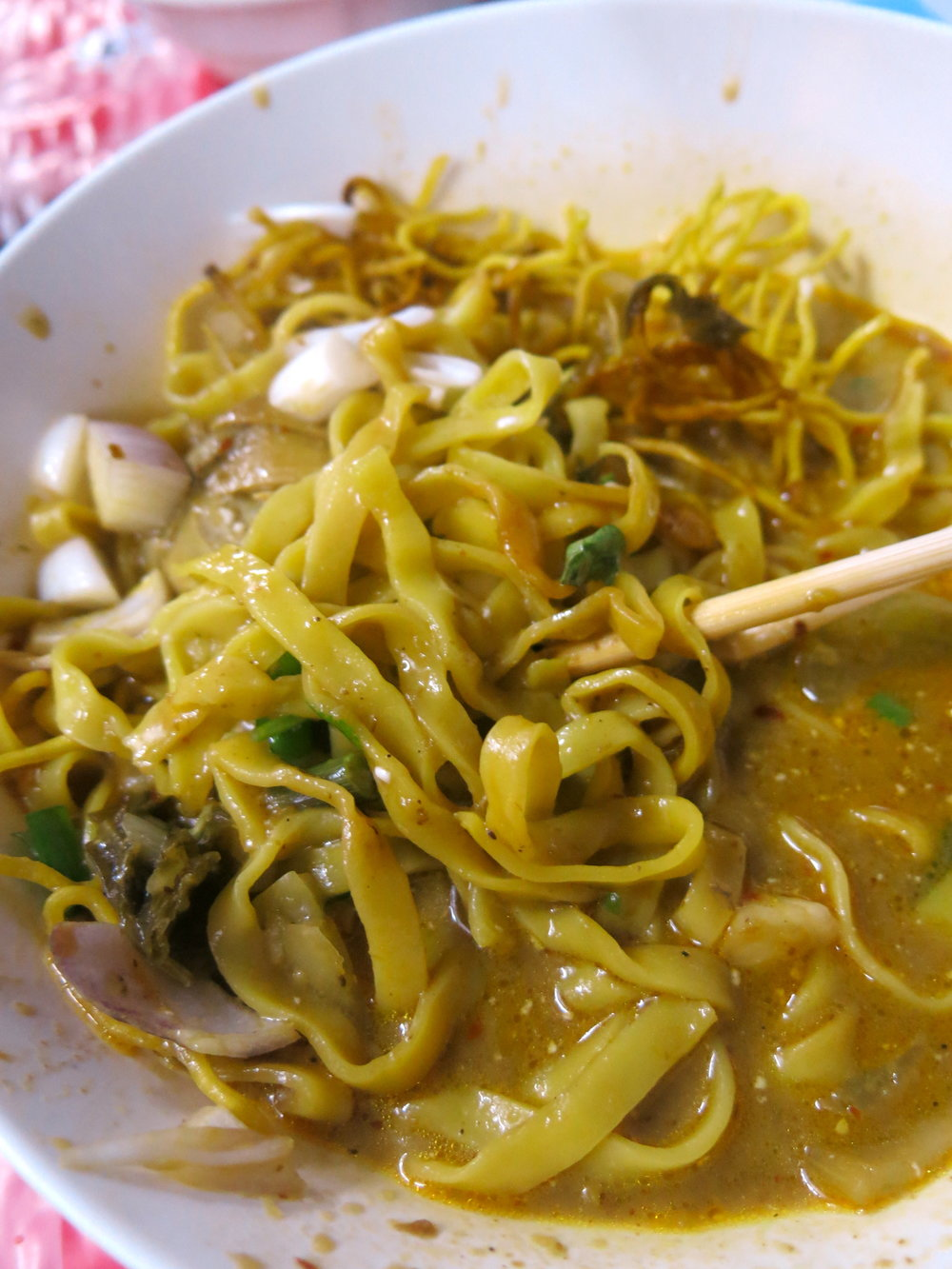Khao Soi is eaten with both chop-sticks for the noodles and a large spoon for the broth