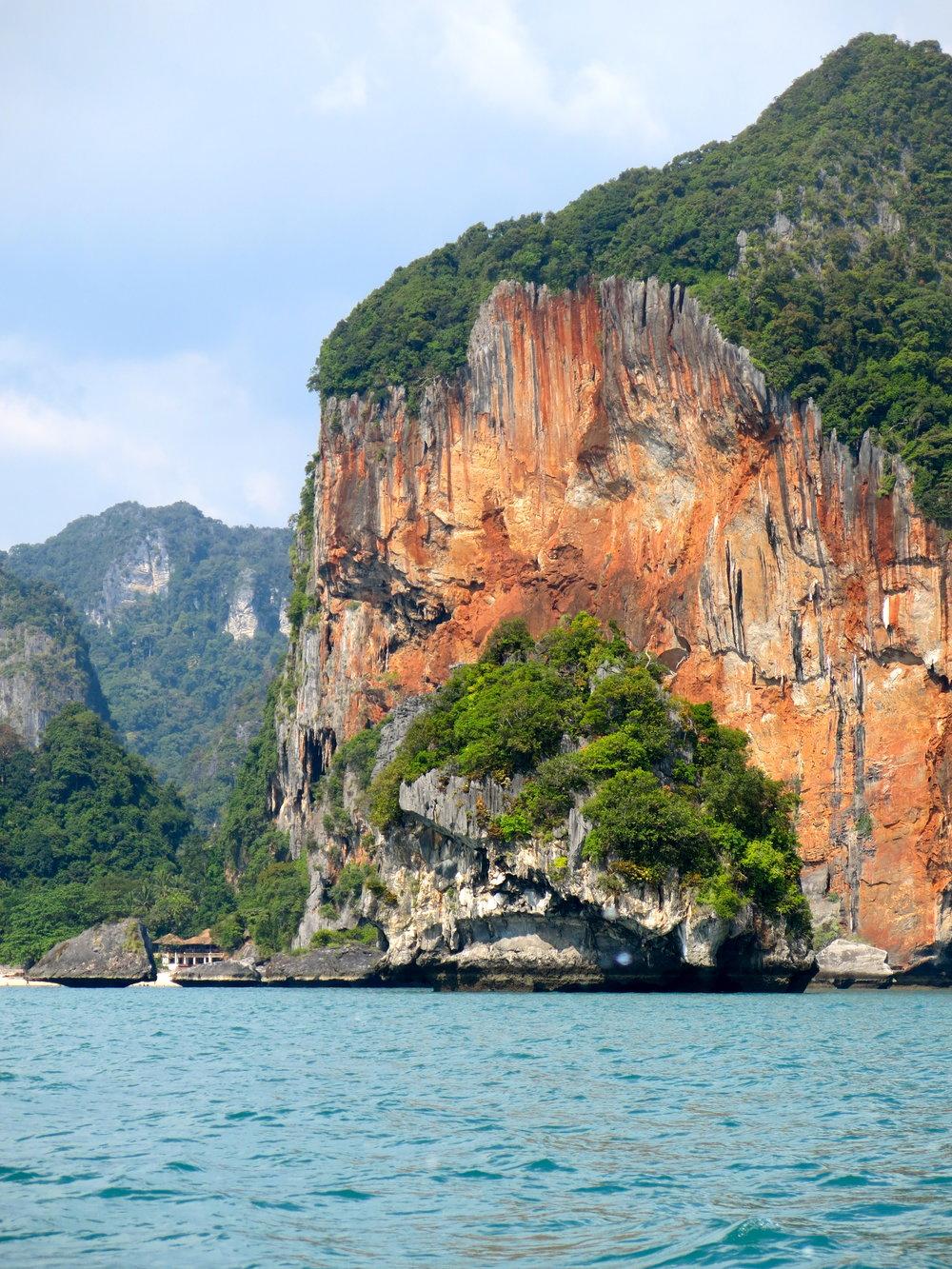 Sailing past the red cliffs near Ao Phra Nang Beach