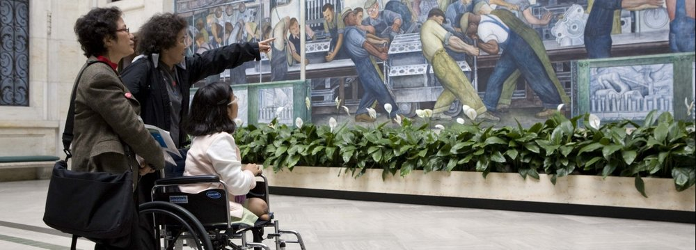 Three women, one in a wheelchair, look at the Diego Reviera murals at the Detroit Institute of Arts.