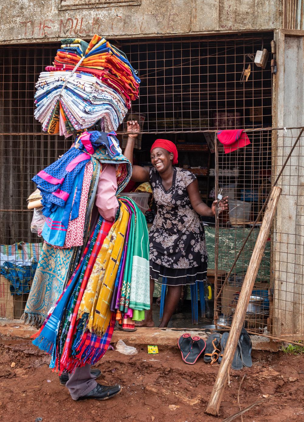 A salesman peddling textiles in Kyebando, Uganda